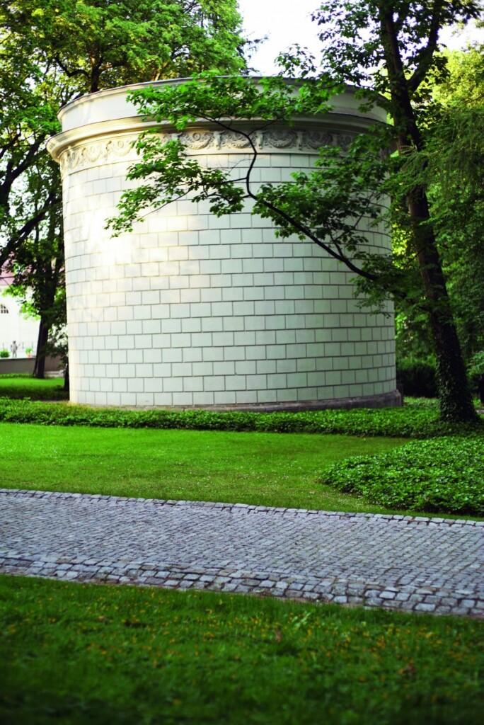 Wśród budynków inspirowanych architekturą rzymską zdecydowanie wyróżnia się wodozbiór zwany Okrąglakiem – budynek wzniesiony na planie koła ipozbawiony zewnętrznych otworów okiennych. W1827 roku został udekorowany przez Piotra Aignera, który dodał mu portyk dwukolumnowy oraz gzyms zdobiony motywem wolich oczek. Całość została upodobniona do grobowca Cecylii Metelli przy Via Appia wRzymie.Fot. Ignacy Fryderyk Heringa