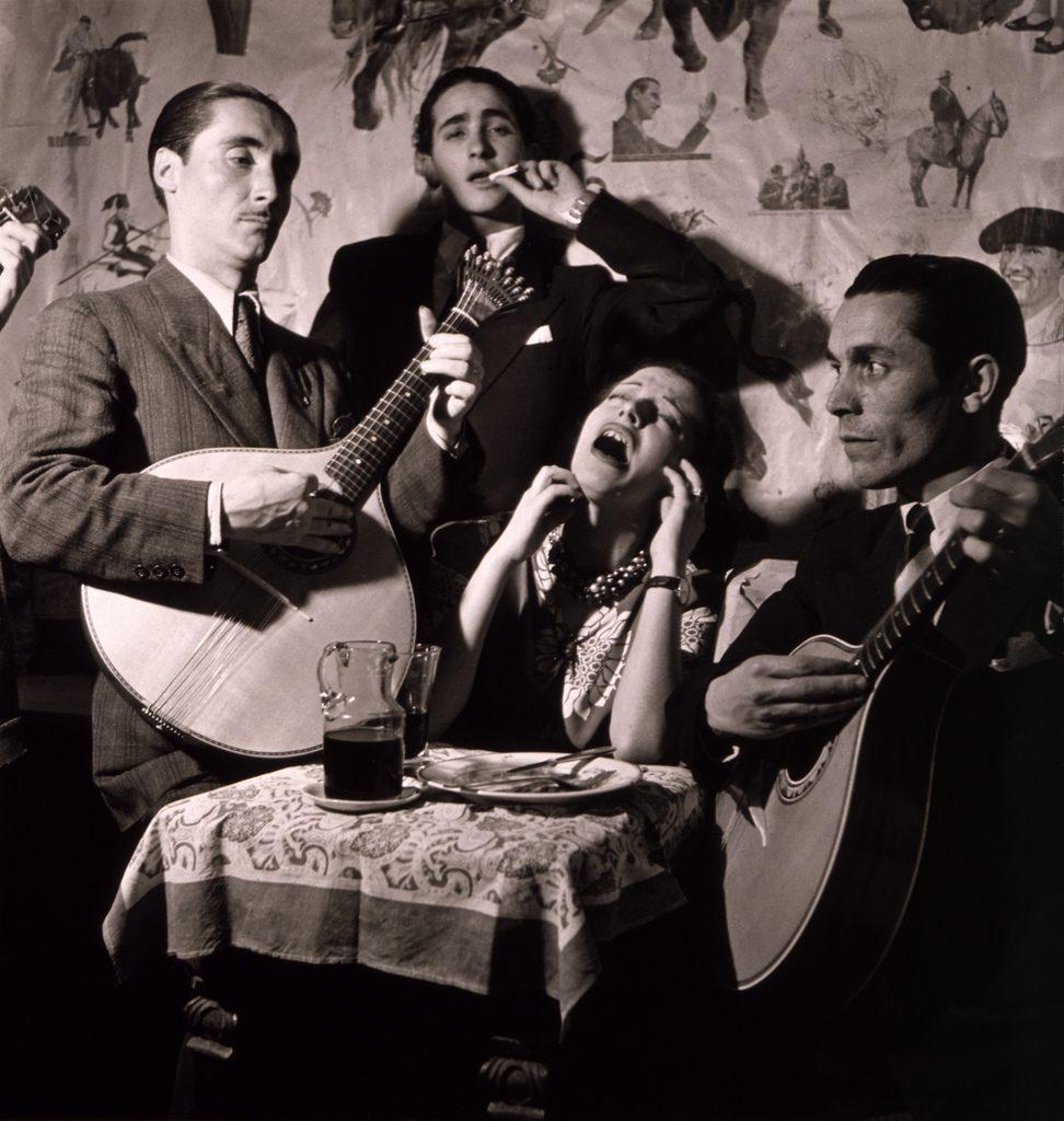 Słowo <em>fado</em> oznacza los, przeznaczenie. Nastrojowe portugalskie pieśni pełne są intesywnych emocji. Śpiewa je zwykle jeden wokalista przy akompaniamencie dwóch gitar. Słowa często opowiadają ożyciu codziennym, traktując oprzyziemnych tematach inadając im poetyckiego wymiaru. Na zdjęciu: muzycy fado wportugalskim lokalu wlatach '40 XX wieku.