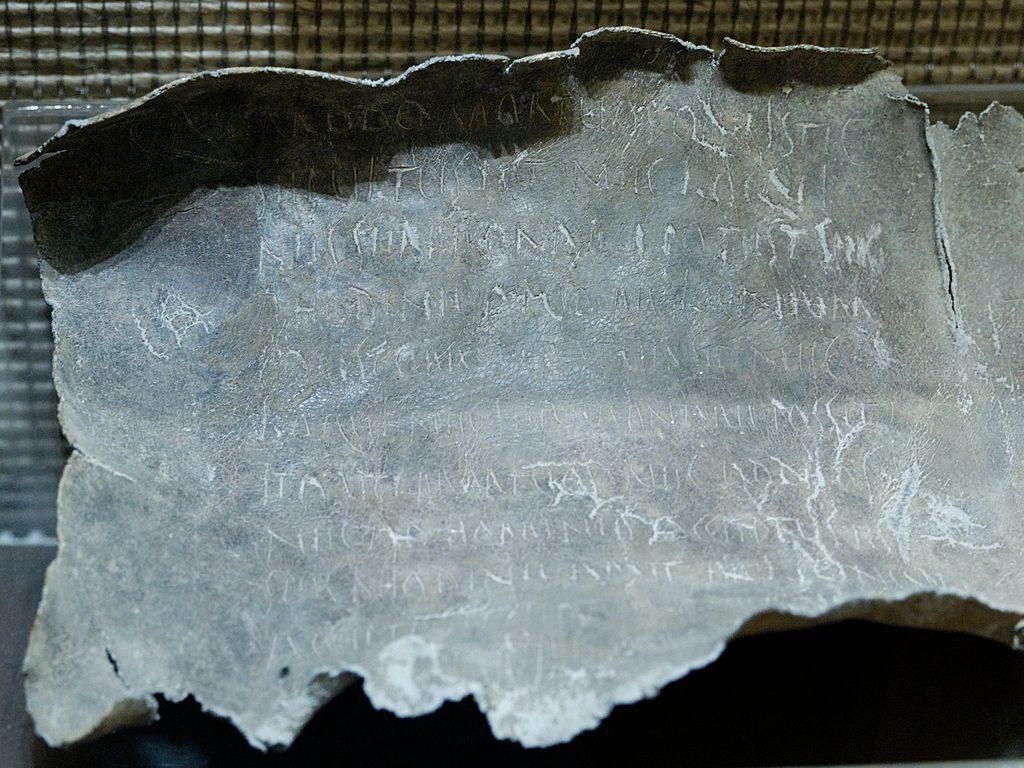 Rzymska ołowiana tabliczka zzaklęciem rzuconym na kobietę oimieniu Rhodine. Wtekście zaklęcia przywoływany jest bóg zaświatów Dis Pater, utożsamiany zPlutonem. Połowa Iwieku p.n.e. Znaleziona wgrobie wpobliżu Via Latina wokolicy Rzymu. Tabliczki zaklęć zpołudniowej Italii różniły się od tej jedynie językiem tekstu ialfabetem, wjakim go zapisano.