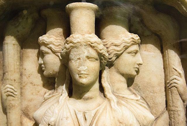 Kult Hekate pochodził zTracji lub zwybrzeży Karii. Było to przedindoeuropejskie bóstwo chtoniczne. Najstarsza świątynia tej bogini znajdowała się wmieście Lagina wdzisiejszej południowo wschodniej Turcji. Przedstawiana była wtrzech postaciach, aw rękach trzymała głowy węża lub psa, ale także pochodnię, miecz isznur. Jej posągi stawiano na rozstajach dróg. Wpóźniejszym okresie wizerunek bogini zmienił się zbudzącego grozę na łagodny, stała się ulubienicą Zeusa, patronką żołnierzy, anawet piastunką dzieci. Dawała bogactwo, siłę isławę. Na zdjęciu: Hekate zPałacu Kinskich wPradze, fot. Zde / Wikimedia, CC BY-SA 3.0