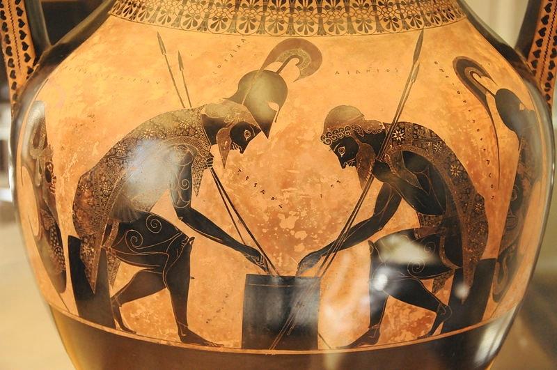 """Jako mężczyzna wdojrzałym wieku (z brodą) Achilles przedstawiony jest na amforze terakotowej wstylu czarnofigurowym zVI w. p.n.e. znanej nam jako """"Achilles iAjas grający wkości""""."""