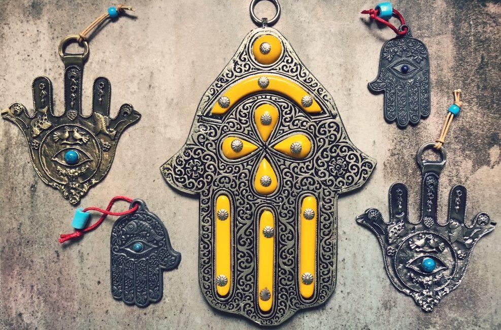 """Wjęzyku arabskim khamsa znaczy 5. Słowo to pochodzi od semickiego źródłosłowu chms. Amulet używany przeciwko """"złemu oku"""" przedstawia zwykle otwartą dłoń, liczą naturalnie 5 palców. Co ciekawe, chamsy żydowskie miewają czasem 6 palców, prawdopodobnie ze względu na zakaz przedstawiania żywych stworzeń obowiązującyn wjudaizmie. Wśrodku dłoni często pojawia się oko – symbol opieki ze strony Stwórcy. Trudno nie doszukać się tu podobieństwa do egipskiego oka Horusa, symbolu odrodzenia ipowrotu do zdrowia. Na zdjęciu chamsy zmojej kolekcji."""