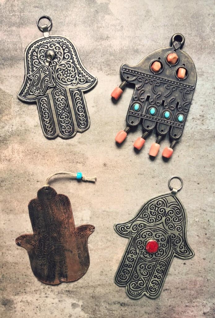 """Chamsy – wróżnych kolorach ikształtach, wykonane zrozmaitych materiałów – mogą stać się ciekawym elementem wystroju wnętrza. Amulety przywiezione przez nas zMaroka iIzraela kupić można teraz wsklepie internetowym Lente wdziale """"Śródziemnomorskie różności""""."""