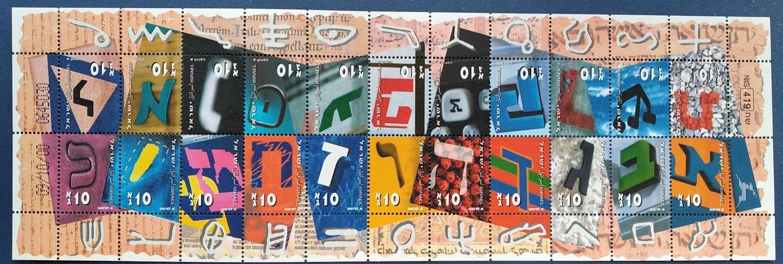 """Alef-Bet czyli alfabet hebrajski. Poczta izraelska lubuje się wnietypowych wydaniach znaczków okolicznościowych. Ta seria z2001 r., wydana wformie arkusika, przedstawia 22 """"główne"""" litery współczesnego alfabetu hebrajskiego (tzw. litery końcowe doczekały się oddzielnego arkusika). Na słynnych przywieszkach pod każdym znaczkiem umieszczono odpowiadającego mu """"protoplastę"""" zalfabetu kanaanejskiego (kolekcja autora)"""
